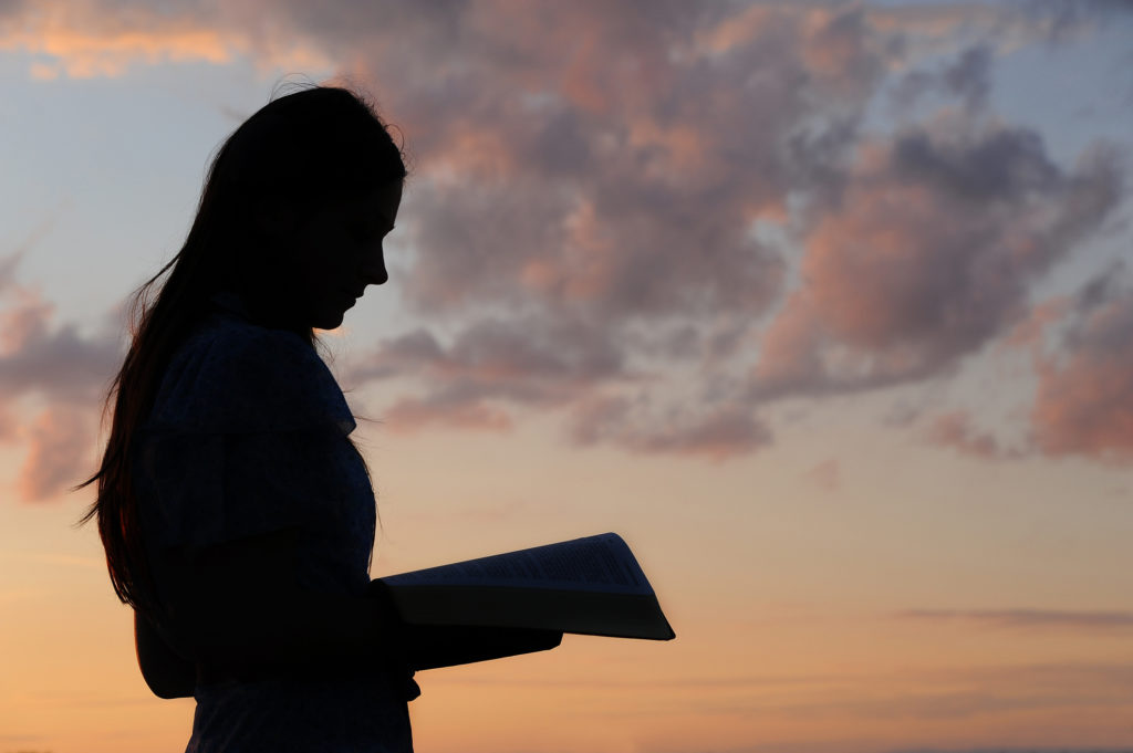 a woman studies against the sunset