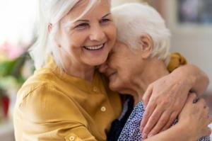 woman embraces elderly woman