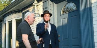 Dr. Jonathan Finkelstien (left) and Rabbi Yanky Baron affix a mezuzah on the new spiritual home of Chabad of Ellicott City