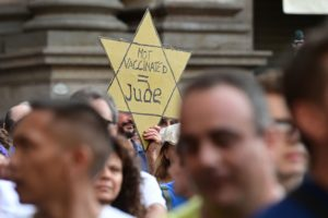 """A protester holds a yellow star reading """"Not Vaccinated = Jew"""" as protesters take part in a demonstration in Milan, Italy, July 24, 2021"""