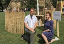 """Architects Jordan Billingsley and Esther Furman crouch in front of their unconventional sukkah, titled """"Woven"""""""