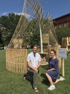 """Architects Jordan Billingsley and Esther Furman crouch in front of their unconventional sukkah, titled """"Woven."""""""